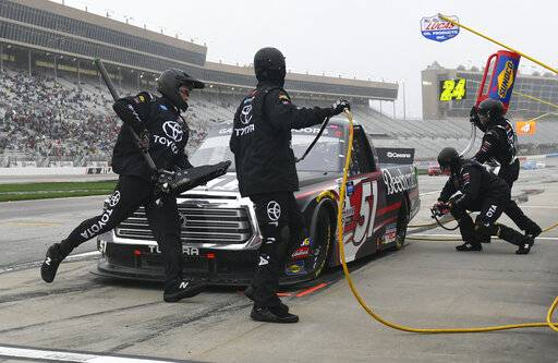 Kyle Busch is tend to by crew members during a pit stop in a NASCAR Truck Series auto race at Atlanta Motor Speedway, Saturday, Feb. 23, 2019, in Hampton, Ga.