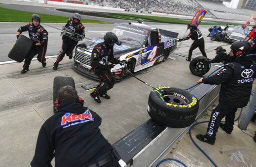Sheldon Creed is tended to by pit crew during a NASCAR Truck Series auto race at Atlanta Motor Speedway, Saturday, Feb. 23, 2019, in Hampton, Ga.