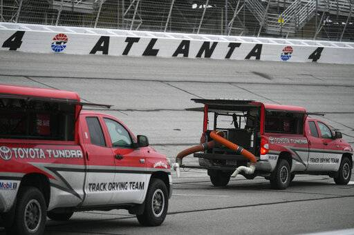 Trucks attempt to dry the track before practice and after qualifying was cancelled before a NASCAR XFINITY auto race at Atlanta Motor Speedway, Saturday, Feb. 23, 2019, in Hampton, Ga.