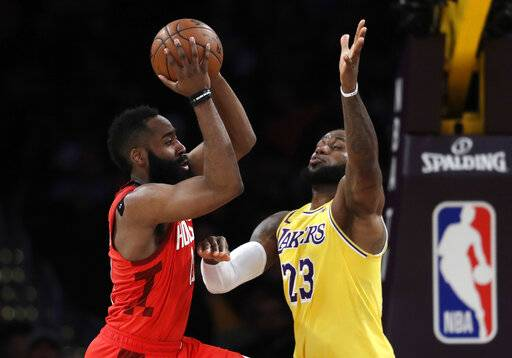 Houston Rockets' James Harden, left, passes the ball next to Los Angeles Lakers' LeBron James during the first half of an NBA basketball game Thursday, Feb. 21, 2019, in Los Angeles. (AP Photo/Marcio Jose Sanchez)