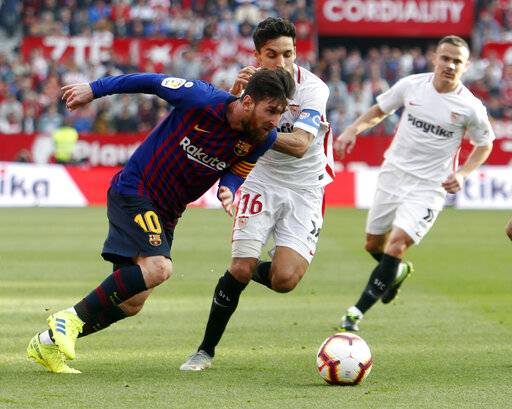 Barcelona forward Lionel Messi and Sevilla's Jeus Navas fight for the ball during La Liga soccer match between Sevilla and Barcelona at the Ramon Sanchez Pizjuan stadium in Seville, Spain. Saturday, February 23, 2019.