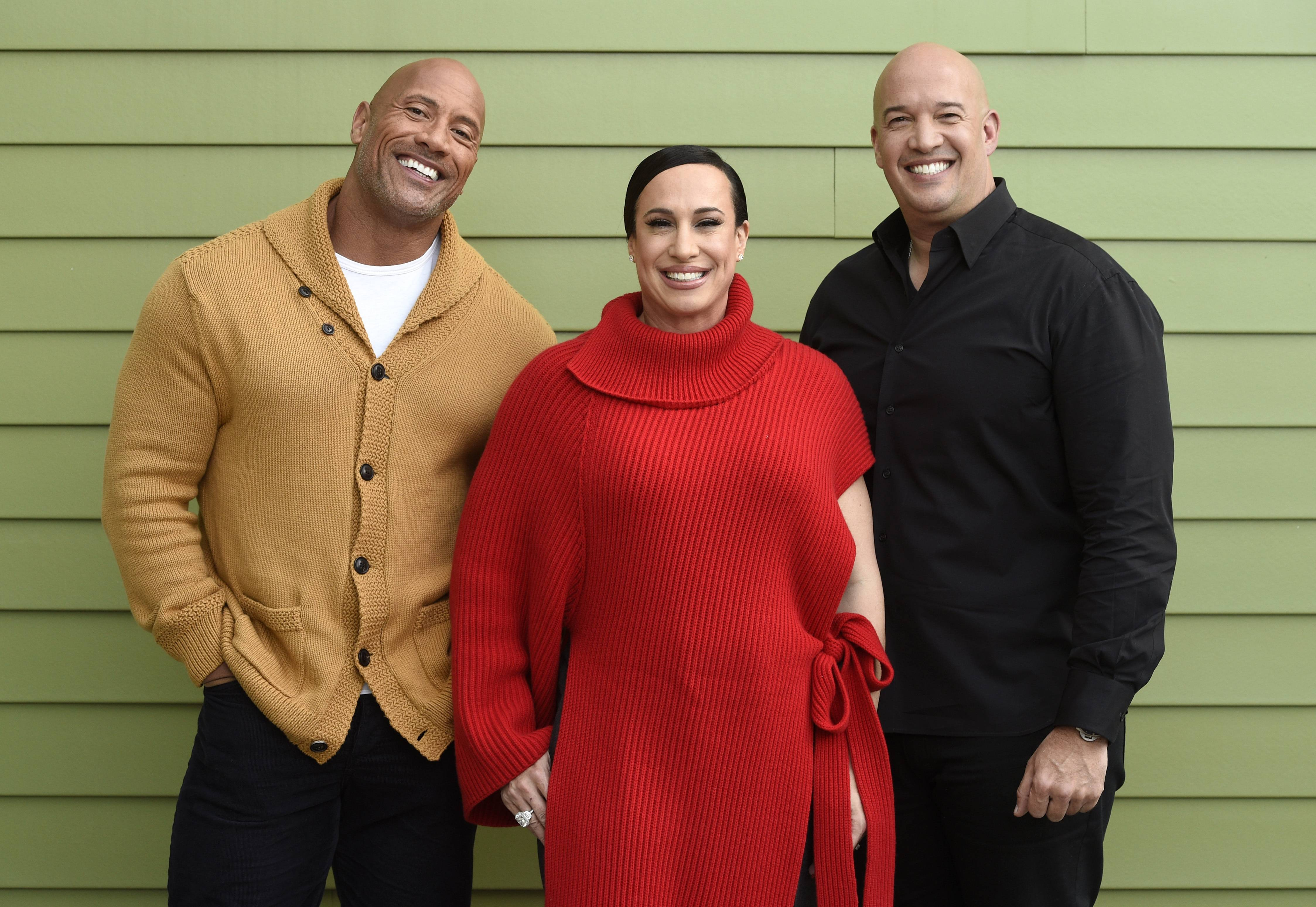 "Dwayne Johnson, left, and Dany Garcia, center, co-founders and co-CEOs of Seven Bucks Productions, and her brother Hiram Garcia, the company's president of production, pose together during the 2019 Sundance Film Festival in Park City, Utah. Johnson put on his independent film producer hat to make his latest film, ""Fighting With My Family."""