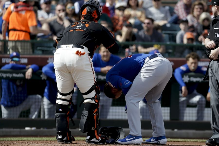 Chicago Cubs' David Bote doubles over after getting hit by a pitch as San Francisco Giants catcher Rene Rivera looks on during the second inning of a spring baseball game in Scottsdale, Ariz., Sunday, Feb. 24, 2019.