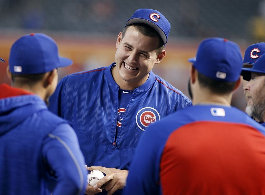 In this Aug. 12, 2017, file photo, Chicago Cubs' Anthony Rizzo, center, laughs as he talks with teammates before a baseball game against the Arizona Diamondbacks, in Phoenix.