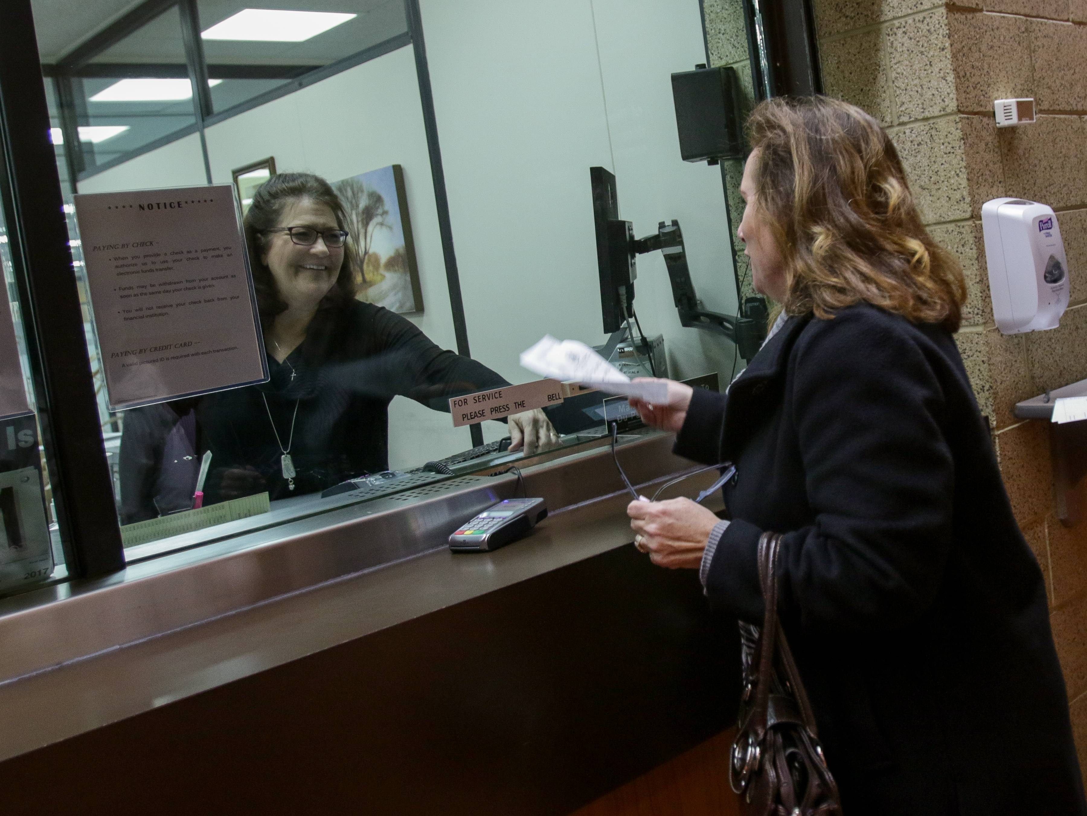 Lynne Nelson with collections, left, helps a Bartlett resident pay her property taxes at DuPage County Treasurer's office in Wheaton.