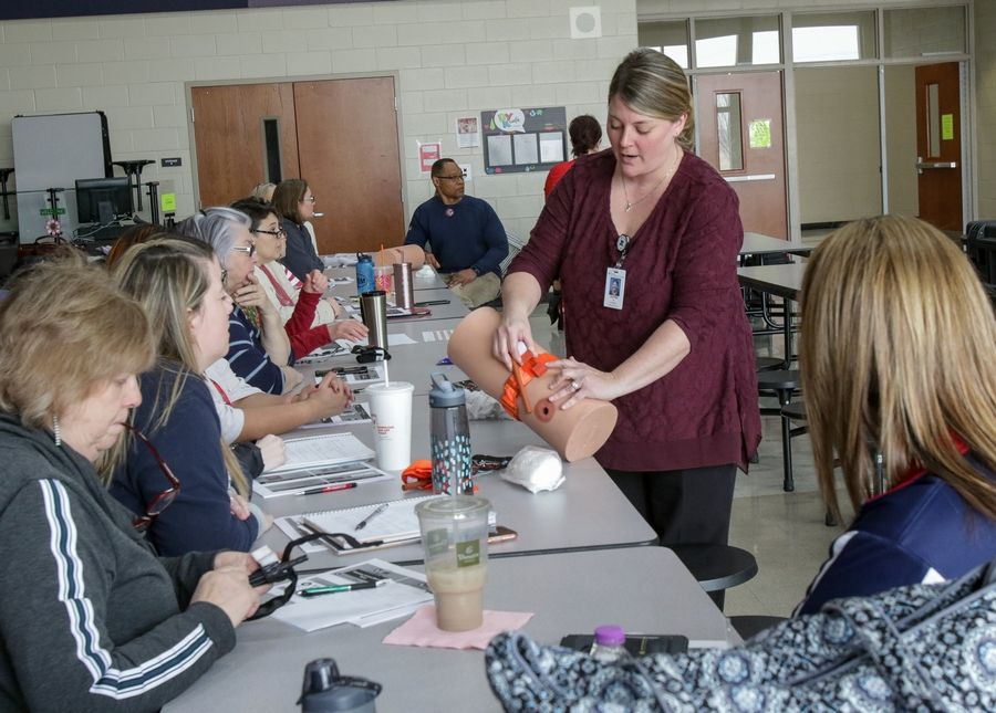 Jennifer Rusz, nurse coordinator at Advocate Good Samaritan Hospital, shows how to tie a tourniquet Friday during a training session called Stop the Bleed on Friday at Herget Middle School in Aurora.