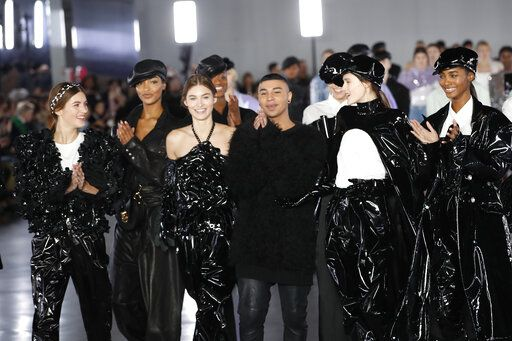 Designer Olivier Rousteing, centre, poses with models at the conclusion of the Balmain ready to wear Fall-Winter 2019-2020 collection, that was presented in Paris, Friday, March 1, 2019.