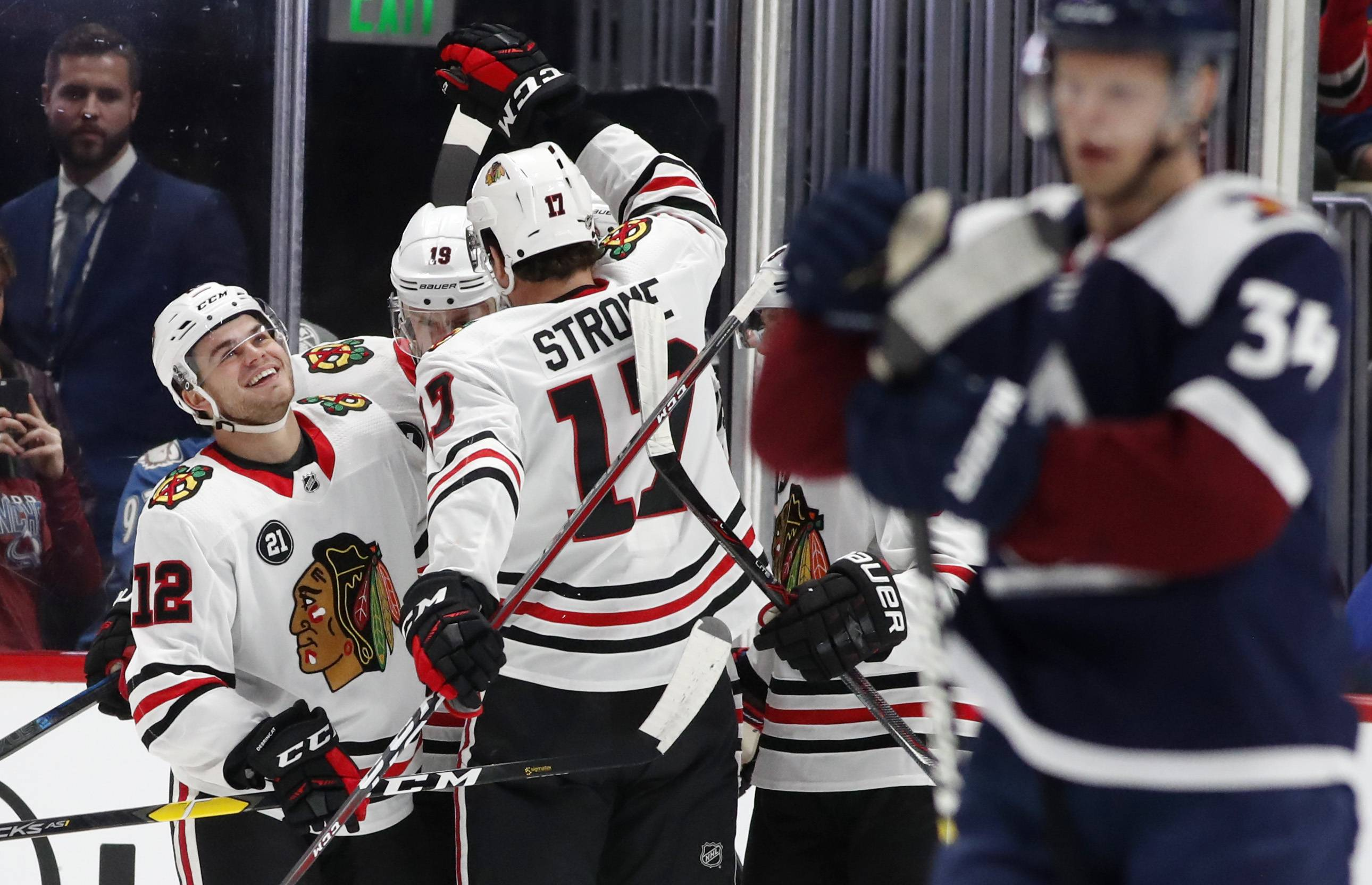 Chicago Blackhawks left wing Alex DeBrincat, left, is congratulated after scoring a goal by centers Jonathan Toews, back right, and Dylan Strome in the first period of an NHL hockey game against the Colorado Avalanche, Saturday, Dec. 29, 2018, in Denver.