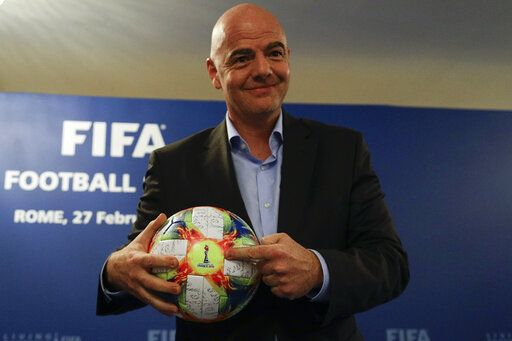 FIFA President Gianni Infantino holds the official ball of the upcoming Women's Soccer World Championship as he poses for photographers during a press conference at the end of an executive committee meeting in Rome, Wednesday, Feb. 27, 2019.