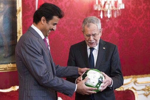 Austrian President Alexander Van der Bellen, right, hands over a football referring to the 2022 FIFA World Cup in Qatar to Qatar's Emir Sheikh Tamim bin Hamad Al Thani, left, prior to their meeting in Vienna, Austria, Tuesday, Mar. 5, 2019.