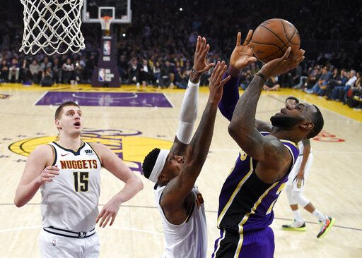 937d31e06b3 Los Angeles Lakers forward LeBron James, right, shoots and scores as Denver  Nuggets forward