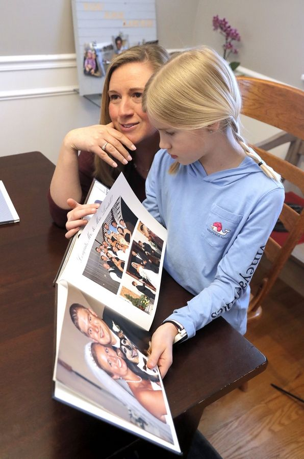 Lisa Lindell, left, and her daughter Julia, 10, flip through a book of pictures of her husband Robert, who died of brain cancer in 2015.