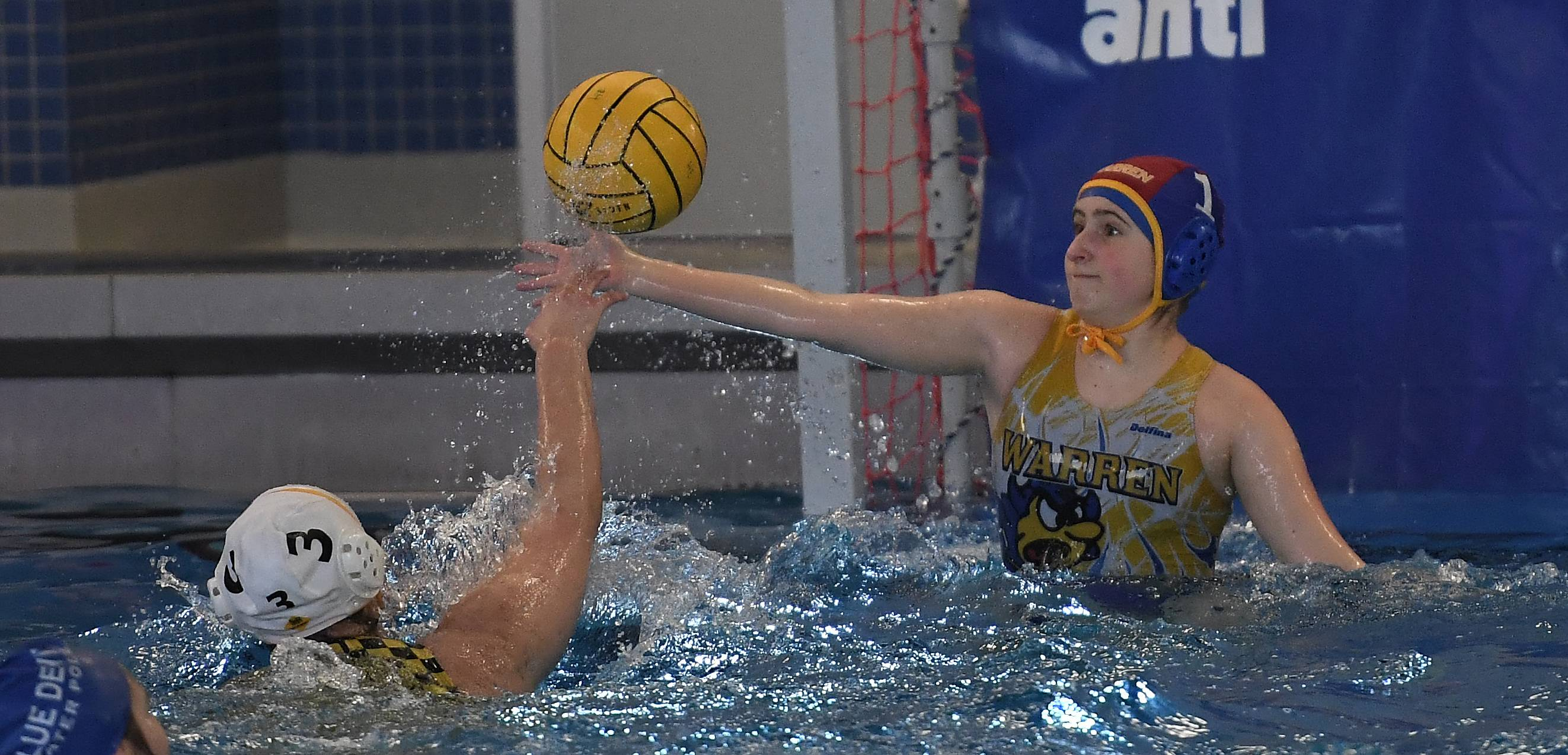 Warren's goalie Nicole Terzian defends as Andrew's Claudia Mietus fires one at her during the Hoffman Estates girls water polo invite on Saturday.