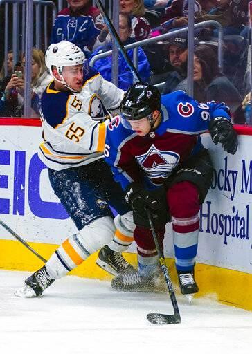 af8a8a4cf12 Colorado Avalanche center Alexander Kerfoot (13) drags down Buffalo Sabres  center Johan Larsson (