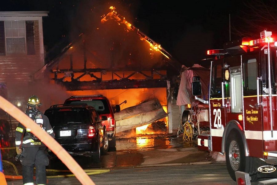 Heavy fire in a home's garage caused several explosions inside the structure Sunday, likely due to propane tanks, Carol Stream firefighters said.