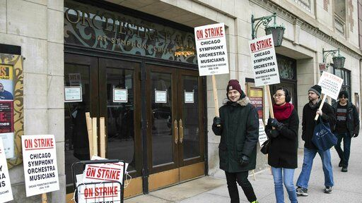 Musicians of the Chicago Symphony Orchestra go on strike and walk the picket line outside the doors of Orchestra Hall on Michigan Avenue, Monday morning, March 11, 2019. (Ashlee Rezin/Chicago Sun-Times via AP)