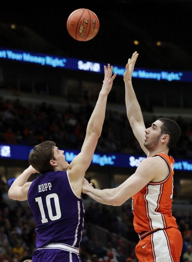 Illinois forward Giorgi Bezhanishvili, right, shoots over Northwestern forward Miller Kopp during the second half of an NCAA college basketball game in the first round of the Big Ten Conference tournament in Chicago, Wednesday. Illinois won 74-69 in overtime.