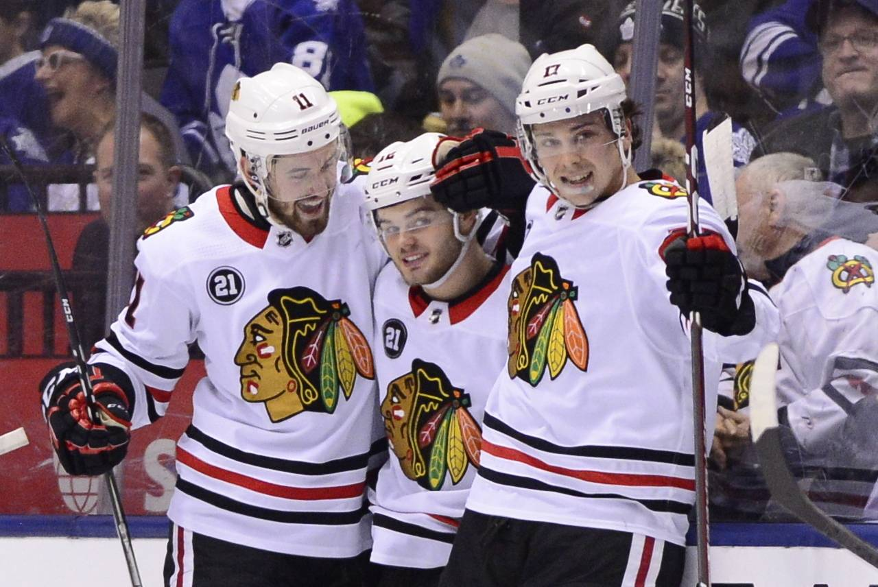 Chicago Blackhawks left wing Alex DeBrincat (12) celebrates his goal with teammates Brendan Perlini (11) and Dylan Strome (17) during the second period of an NHL hockey game Wednesday, March 13, 2019, in Toronto. (Frank Gunn/The Canadian Press via AP)