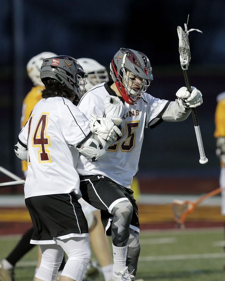 Schaumburg's Nick Woodworth, left, celebrates with Mark Dewees after his goal during boys lacrosse at Schaumburg High School Wednesday.