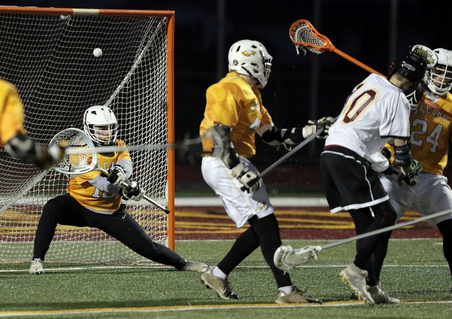 Schaumburg's Chris Kula, right, scores on Jacobs' Cameron Mollsen during boys lacrosse at Schaumburg High School Wednesday.