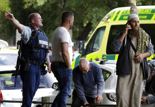 Police attempt to clear people from outside a mosque in central Christchurch, New Zealand, Friday, March 15, 2019. Many people were killed in a mass shooting at a mosque in the New Zealand city of Christchurch on Friday, a witness said. Police have not yet described the scale of the shooting but urged people in central Christchurch to stay indoors.