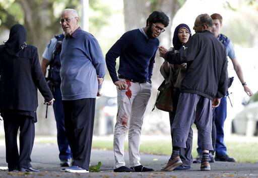 People stand across the road from a mosque in central Christchurch, New Zealand, Friday, March 15, 2019. A witness says a number of people have been killed in a mass shooting at a mosque in the New Zealand city of Christchurch; police urge people to stay indoors.