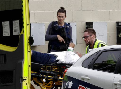 An armed police officer watches as a man is taken by ambulance staff from a mosque in central Christchurch, New Zealand, Friday, March 15, 2019.   Multiple people were killed in mass shootings at two mosques full of people attending Friday prayers, as New Zealand police warned people to stay indoors as they tried to determine if more than one gunman was involved.