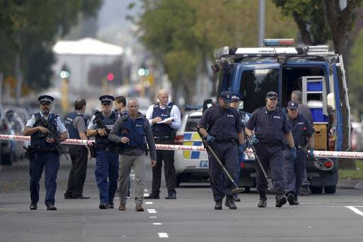 Police officers search the area near the Masjid Al Noor mosque, site of one of the mass shootings at two mosques in Christchurch, New Zealand, Saturday, March 16, 2019.