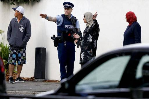 A police officer directs pedestrians neat the site of one of the mass shootings at two mosques in Christchurch, New Zealand, Saturday, March 16, 2019.