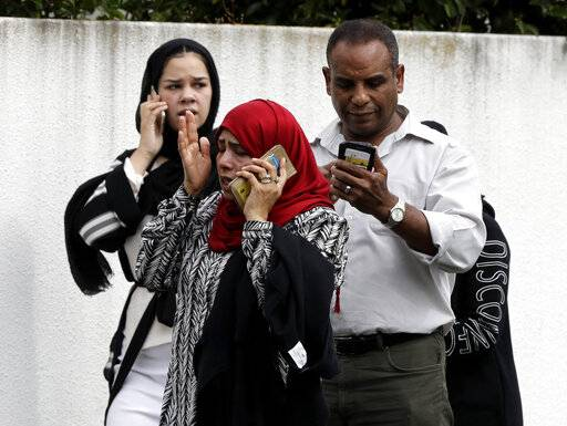 People wait outside a mosque in central Christchurch, New Zealand, Friday, March 15, 2019. Many people were killed in a mass shooting at a mosque, a witness said.