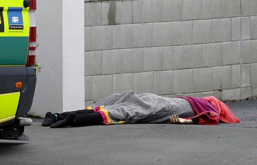 A body lies on the footpath outside a mosque in central Christchurch, New Zealand, Friday, March 15, 2019, following a mass shooting.