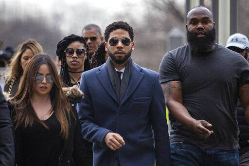 Empire actor Jussie Smollett, center, arrives at the Leighton Criminal Court Building for his hearing on Thursday, March 14, 2019, in Chicago. Smollett is accused of lying to police about being the victim of a racist and homophobic attack by two men on Jan. 29 in downtown Chicago.   (Ashlee Rezin/Chicago Sun-Times via AP)