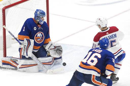 New York Islanders goaltender Thomas Greiiss, left, makes a save against Montreal Canadiens center Jesperi Kotkaniemi, upper right, during the third period of an NHL hockey game, Thursday, March 14, 2019, in Uniondale, N.Y.