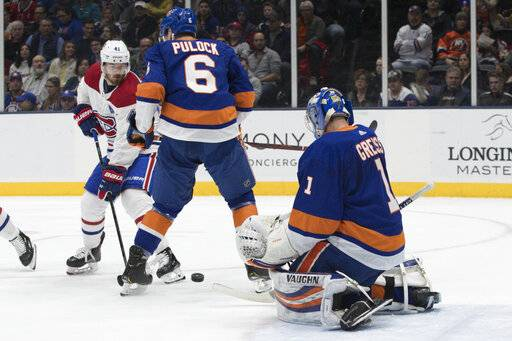 New York Islanders goaltender Thomas Greiss (1) and defenseman Ryan Pulock (6) make a save against Montreal Canadiens left wing Paul Byron (41) during the first period of an NHL hockey game, Thursday, March 14, 2019, in Uniondale, N.Y.