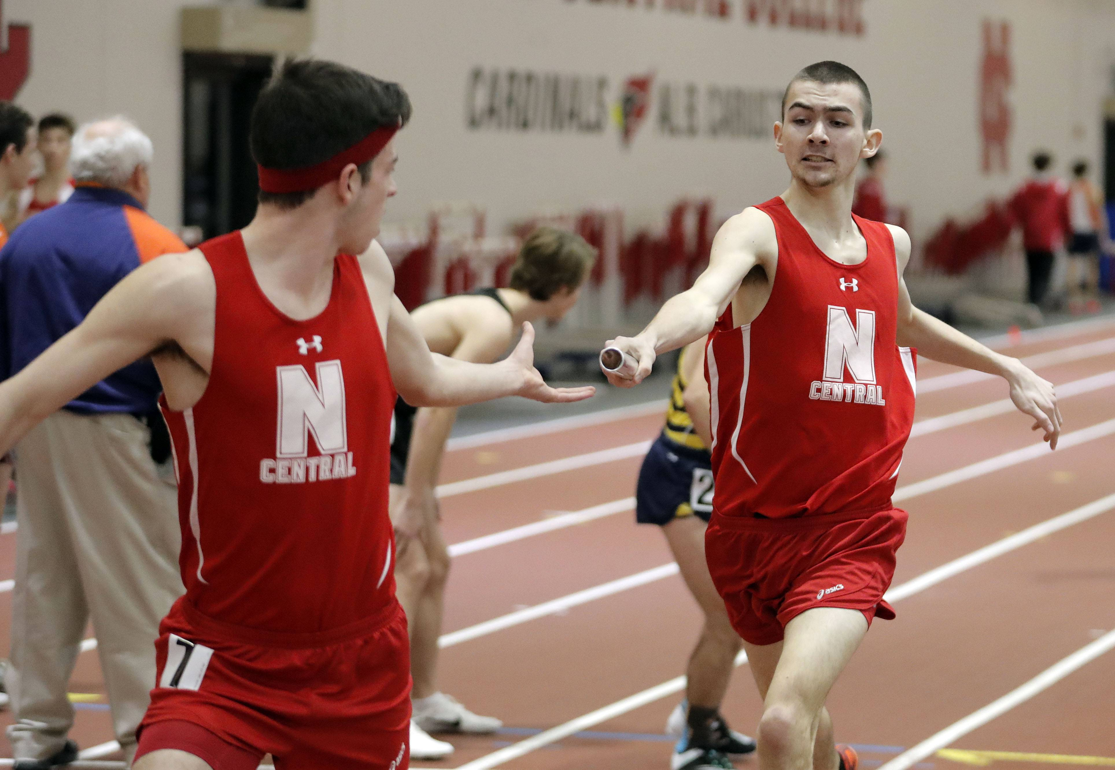 Naperville Central's Aaron benson, right, hands to Seth Klein-Collins in the 4x800-meter relay during the DuPage Valley Conference boys track meet at North Central College in Naperville Friday.