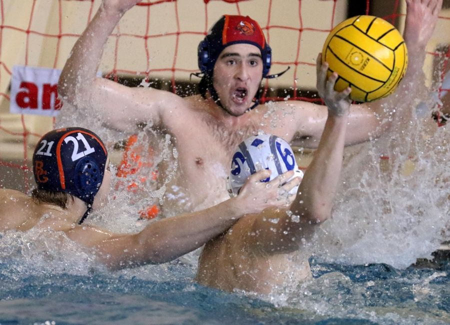 Warren's Sam Aiello, right, prepares to shoot as Buffalo Grove's Michael Goubine, left, defends and Buffalo Grove goalie Brandon Newman blocks during varsity boys water polo at Buffalo Grove Friday night.