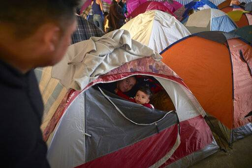 In this March 5, 2019, image, Ruth Aracely Monroy, center, looks out of the family's tent alongside her 10-month-old son, Joshua, as her husband, Juan Carlos Perla, left, passes inside a shelter for migrants in Tijuana, Mexico. After fleeing violence in El Salvador and requesting asylum in the United States, the family was returned to Tijuana to await their hearing in San Diego. They were one of the first families to contend with a new policy that makes asylum seekers stay in Mexico while their cases wind through U.S. immigration courts.
