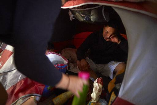 In this March 5, 2019, image, Juan Carlos Perla reacts as he and his wife, Ruth Aracely Monroy, left, searches for medicine in their tent for their 10-month-old son with a cold inside a shelter for migrants in Tijuana, Mexico. Many asylum seekers are now forced to wait in Mexico while their cases wind through U.S. immigration courts.
