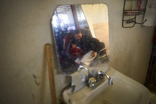 "In this March 5, 2019, image, Juan Carlos Perla holds his 10-month-old son, Joshua, reflected in a mirror inside a shelter for migrants in Tijuana, Mexico. ""Our fear is that we lose our case and get deported� to El Salvador, Perla said. ""That's suicide for me, my wife and my children.�"