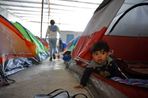 In this March 12, 2019, image, 10-month-old Joshua Perla looks out from the family's tent in a shelter for migrants in Tijuana, Mexico. Asylum seekers are now forced to wait in Mexico while their cases wind through U.S. immigration courts. They often struggle to find legal advice and say they feel unsafe. The Trump administration introduced the new policy in January amid a surge of asylum-seeking families from Guatemala, Honduras and El Salvador arriving at the Mexican border.