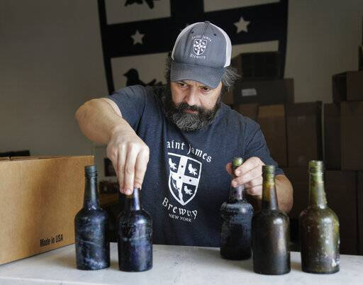 In this March 4, 2019, photo, Jamie Adams shows some intact beer bottles recovered from the shipwreck of the SS Oregon at his St. James Brewery in Holbrook, N.Y. Adams created an ale called Deep Ascent using the yeast from the bottles recovered from the Liverpool-to-New York luxury liner that sank off Fire Island in 1886.