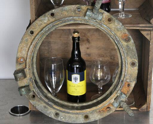 This March 4, 2019, photo shows a porthole recovered from the SS Oregon, a Liverpool-to-New York luxury liner that sank off Fire Island in 1886, at St. James Brewery in Holbrook, N.Y. Long Island brewer Jamie Adams recently introduced an ale called Deep Ascent at a New York craft beer festival after he created it, using the yeast from the bottles recovered from the SS Oregon.