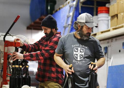 In this March 4, 2019, photo, brewery founder Jamie Adams, right, and John Condzella, left, bottle a batch of their Dubbel beer at the St. James Brewery in Holbrook, N.Y. Adams recently introduced an ale called Deep Ascent at a New York craft beer festival after he created it, using the yeast from the bottles recovered from the SS Oregon, a Liverpool-to-New York luxury liner that sank off Fire Island in 1886.