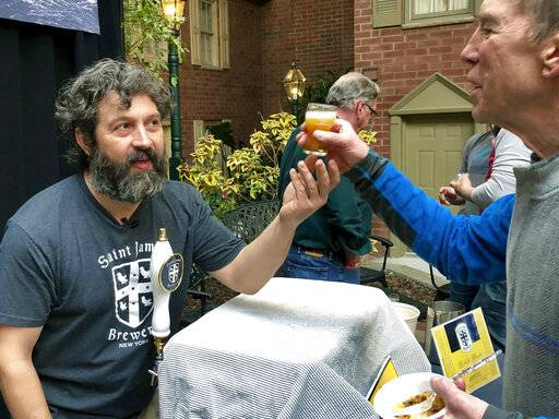 """In this March 9, 2019 photo, Jamie Adams, left, hands out a sample of his new ale called """"Deep Ascent"""" at the New York State Craft Brewers Festival in Albany, N.Y. Adams, a former Wall Street trader who opened Saint James Brewery in Long Island nearly two decades ago, says his beer grew out of his love of scuba diving. It was brewed with yeast extracted from bottles he and fellow divers salvaged from the SS Oregon, a luxury liner from Liverpool to New York that collided with a schooner and sank off Fire Island in 1886."""