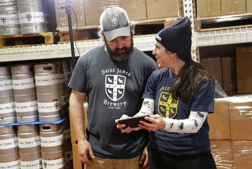 In this March 4, 2019, photo, Jamie Adams and his wife Rachel Adams look at an image of a banner for their new beer, Deep Ascent, at their St. James Brewery in Holbrook, N.Y. Adams recently introduced an ale called Deep Ascent at a New York craft beer festival after he created it, using the yeast from the bottles recovered from the SS Oregon, a Liverpool-to-New York luxury liner that sank off Fire Island in 1886.