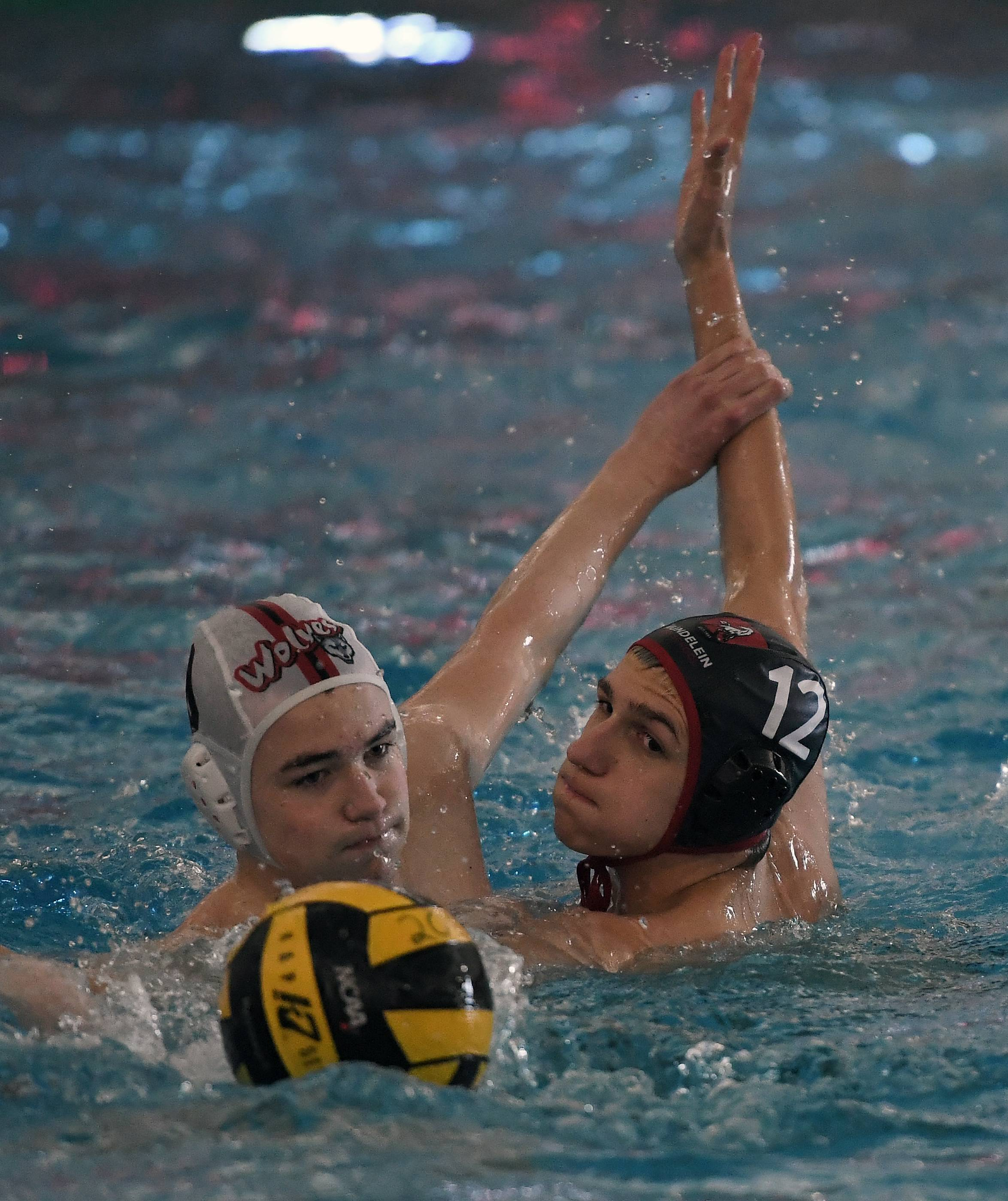 Mundelein's Jake Garcia battles with a Niles West player in the boys water polo varsity invite at Mundelein High School on Saturday.