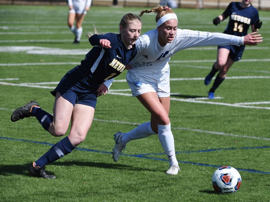 St. Charles North's Ali Wessel, right, tries to hold off Neuqua Valley's Julia Rushing as they pursue the ball during Saturday's match at Commissioner's Park in Naperville.