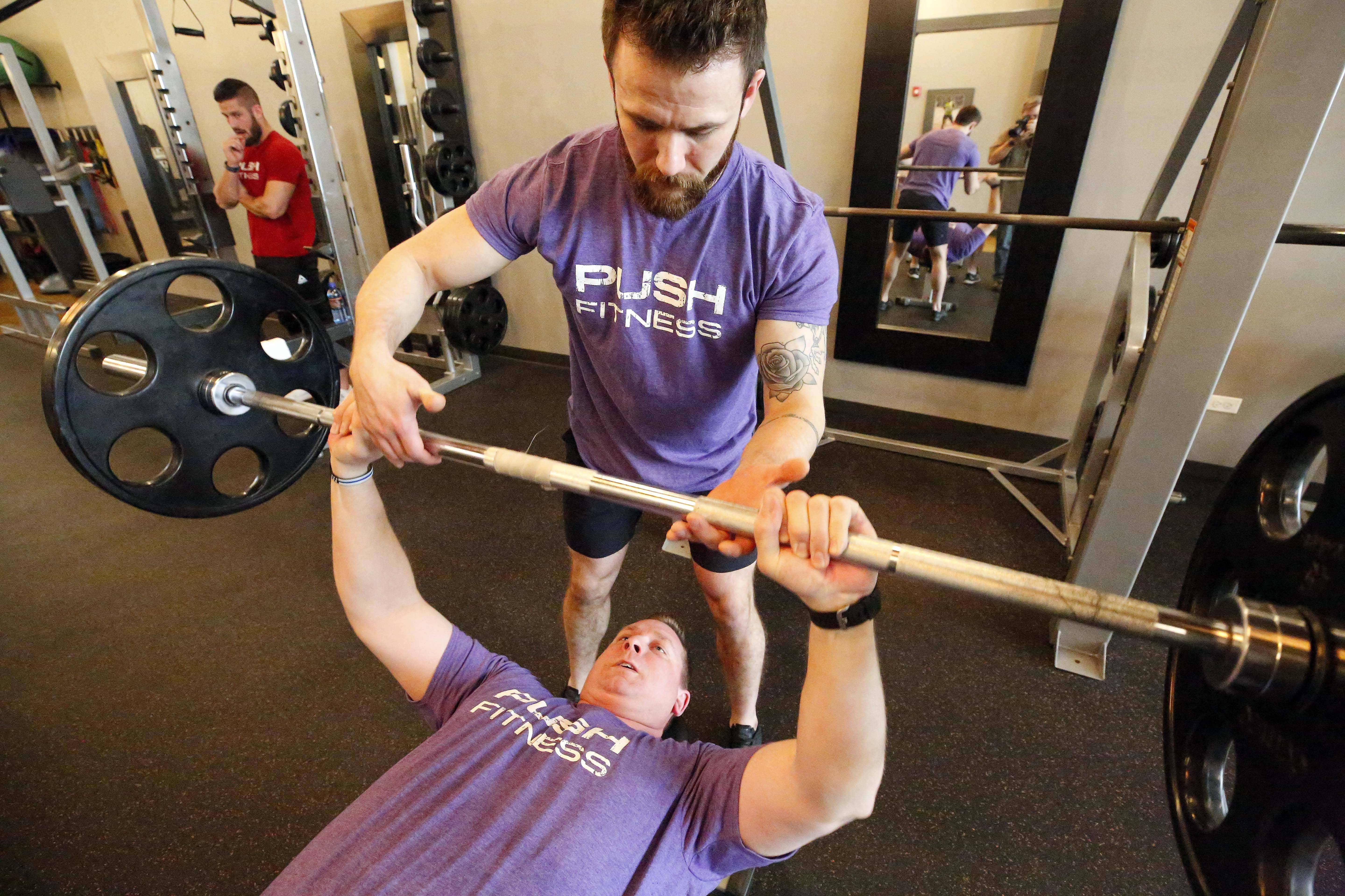 Fittest Loser participant Rick Meyers pumps weights to build strength with trainer Patrick Stille