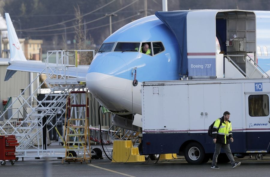 A worker walks past an avionics truck parked next to a Boeing 737 MAX 8 airplane being built for TUI Group at Boeing Co.'s Renton Assembly Plant in Renton, Wash. The U.S. An investigation of how the 737 Max was certified to fly passengers began before the latest crash in Ethiopia involving the new jet, according to sources speaking to Bloomberg News.
