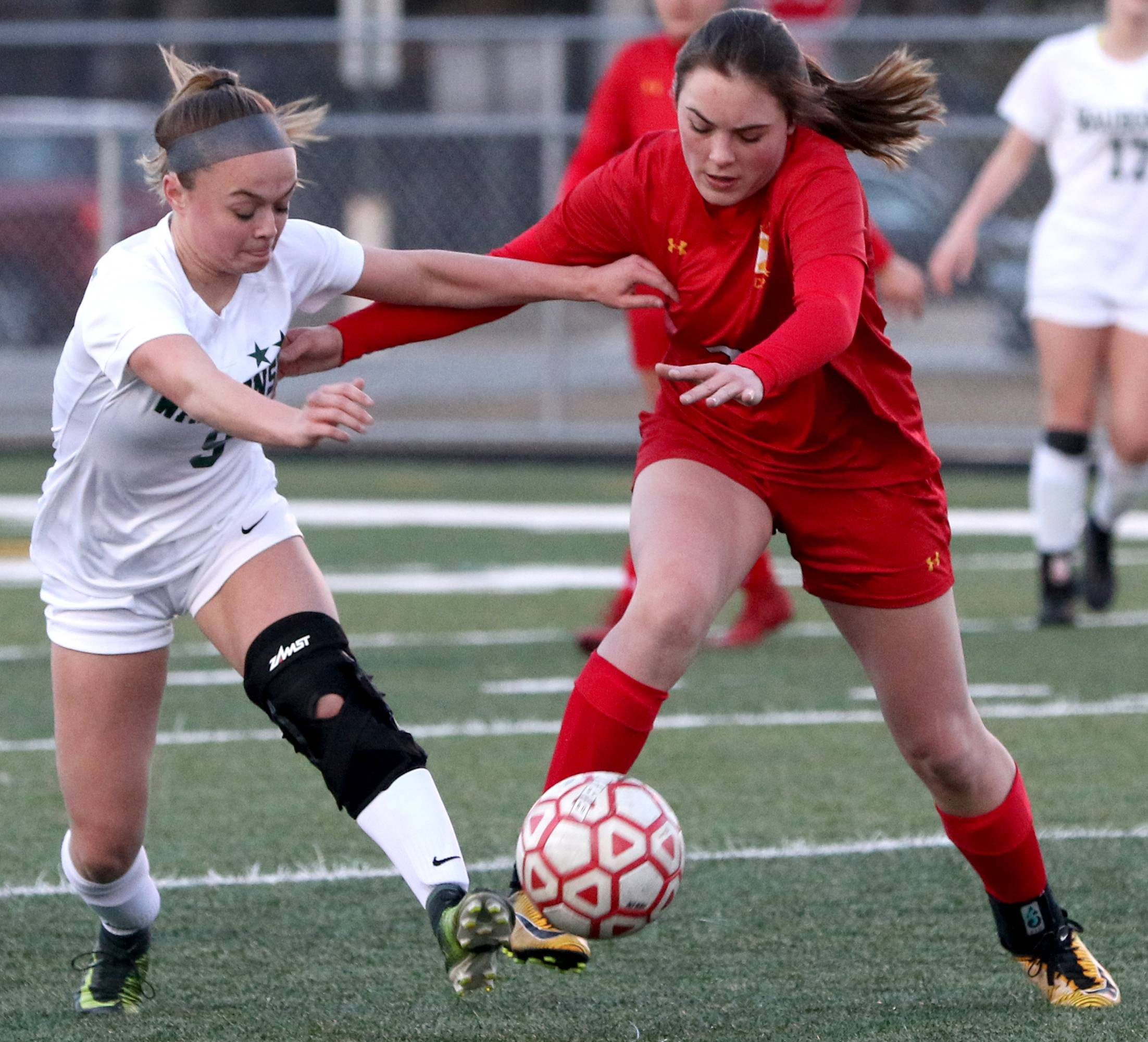 Batavia's Ashley Whelpley, right, and Waubonsie Valley's Roxy Zieba race to the ball at Batavia's Bulldog Stadium Monday.